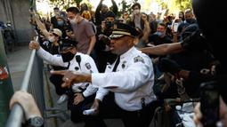 Deputi Komisaris Polisi Philadelphia, Melvin Singleton (tengah) berlutut dan meminta polisi lain bergabung dengannya saat pawai menyerukan keadilan atas kematian George Floyd di luar markas besar Kepolisian Philadelphia di Philadelphia, Senin (1/6/2020). (AP/Matt Slocum)