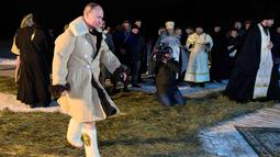 Presiden Rusia Vladimir Putin berpakaian mantel kulit domba berjalan untuk berendam di air dingin selama perayaan Hari Epiphany di Danau Seliger di desa Svetlitsa, Rusia (19/1). (Alexei Druzhinin, Sputnik, Kremlin Pool Photo via AP)