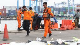 Petugas mengangkat kantung jenazah korban jatuhnya pesawat Lion Air PK LQP di Pelabuhan JICT 2, Jakarta, Senin (5/11). Hingga hari kedelapan jatuhnya pesawat Lion Air PK-LQP, tim SAR gabungan terus mencari korban. (Liputan6.com/Helmi Fithriansyah)