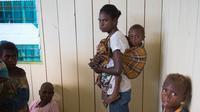 Seorang wanita menggendong anaknya untuk menunggu perawatan medis di klinik setempat di desa Ayam distrik Asmat, di provinsi Papua Barat (26/1). (AFP/Bay Ismoyo)