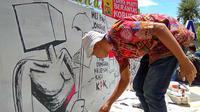 Unek-unek para seniman mural yang tergabung dalam Komunitas Tikar Pandan tumpah ruah di atas tripleks yang disandarkan di tembok Taman Bustanulsalatin (Liputan6.com/Rino Abonita)