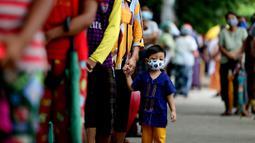 Seorang anak yang mengenakan masker mengantre saat menunggu giliran untuk mendapatkan pengecekan medis dalam kampanye pemeriksaan kesehatan dan pelacakan kontak di Yangon, Myanmar, pada 8 September 2020. Myanmar melaporkan 92 kasus baru COVID-19 pada Selasa (8/9) pagi waktu setempat. (Xinhua/U Aung