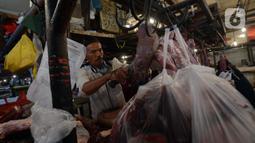 Pedagang memotong daging sapi saat melayani pembeli di Pasar Perumnas, Jakarta, Selasa (19/1/2021). Pedagang daging sapi akan mogok jualan sebagai bentuk protes kepada pemerintah karena tingginya harga daging sapi di pasar sejak awal tahun. (merdeka.com/Imam Buhori)