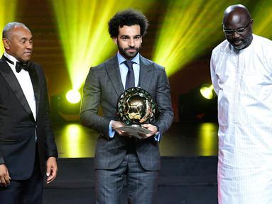 Winger Liverpool, Mohamed Salah berpose setelah menerima penghargaan Pemain Terbaik Afrika 2018 dalam malam penghargaan di Dakar, Senegal, Selasa (8/1). Pemain asal Mesir tersebut menang untuk kedua kalinya secara beruntun. (SEYLLOU/AFP)