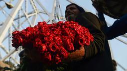 Pedagang merapihkan bunga mawar saat mereka menunggu pelanggan di pasar bunga grosir di Kolkata, India (7/2). Jelang perayaan hari Valentine, bunga mawar banyak diburu dari tanggal 7 Februari dengan ditandai dengan Rose Day. (AFP Photo/Dibyangshu Sarkar)