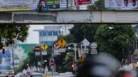 Alat peraga kampanye (APK) terpasang di jembatan penyeberangan orang (JPO) kawasan Mampang, Jakarta, Rabu (27/2). APK masih menghiasi JPO di Ibu Kota meski KPU telah melarang pemasangan di sarana dan prasarana publik. (Liputan6.com/Faizal Fanani)