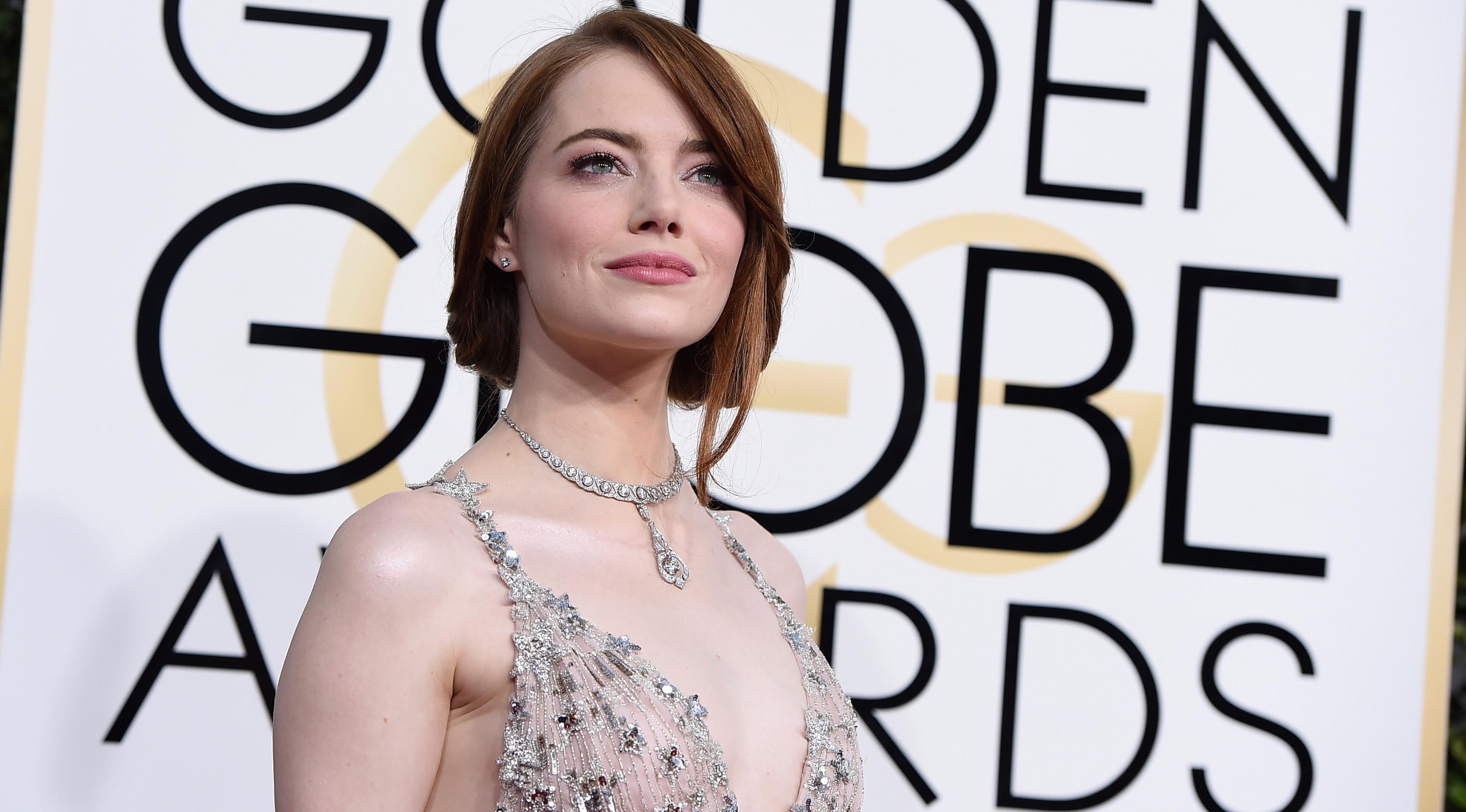 Aktris Emma Stone memilih gaun bergaris leher rendah saat menghadiri Golden Globe Awards 2017 di California, Minggu (8/1).Gaun tanpa lengan bernuansa merah muda itu bertabur pernak-pernik bintang yang mengilap.  (Photo by Jordan Strauss/Invision/AP)