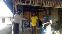 Foto: Dua anggota Bhabinkamtibmas Polsek Paga, SIKKA, NTT saat mengantar daging hewan kurban ke warga kurang mampu (Liputan6.com/Dion)