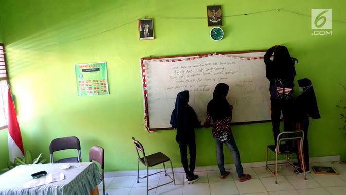 Sejumlah siswi memasang papan tulis yang jatuh akibat gempa di dalam kelas SMP Negeri 6 Palu, Sulawesi Tengah, Senin (8/10). Pascagempa dan tsunami Palu, pihak sekolah melakukan pendataan untuk mengetahui jumlah siswa sekolah. (Liputan6.com/Fery Pradolo)