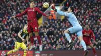Kiper Southampton Alex McCarthy berusaha menangkap bola sundulan penyerang Liverpool, Roberto Firmino pada pertandingan Liga Inggris di Stadion Anfield, Sabtu (1/2/2020). Liverpool menang telak 4-0 atas Southampton. (AP Photo/Jon Super)
