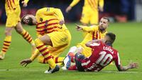 Bek Barcelona, Gerard Pique, terjatuh saat berebut bola dengan pemain Atletico Madrid, Angel Correa, pada laga Liga Spanyol di Stadion Wanda Metropolitano, Minggu (22/11/2020). Barcelona takluk dengan skor 1-0. (AP/Bernat Armangue)