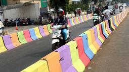 Pengendara motor melintasi di sisi pemisah jalan di Jalan Raya Ragunan sekitar Pasar Minggu, Jakarta, Selasa (24/7). Di kawasan ini pemisah jalan di cat warna warni sehingga terlihat lebih semarak. (Liputan6.com/Helmi Fithriansyah)