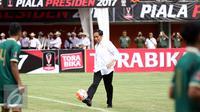 Presiden Joko Widodo menendang bola ke arah pemain PSS saat pembukaan turnamen Piala Presiden 2017 di Stadion Maguwoharjo, Sleman, Sabtu (4/2). 31.000 penonton menyaksikan laga pembuka turnamen Piala Presiden 2017. (Liputan6.com/Helmi Fithriansyah)