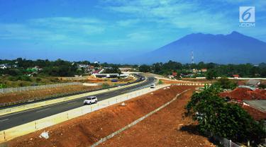 Kendaraan melintasi tol dengan latar belakang Gunung Salak saat Tol Fungsional Bocimi seksi 1 Ciawi-Cigombong dibuka menuju arah Ciawi di kawasan Ciawi Bogor (20/6). (Merdeka.com/ Arie Basuki)