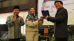 Presiden PKS Mohamad Sohibul Iman bersama Ketua Fraksi PKS DPR Jazuli Juwaini memberikan plakat kepada putri Kasman Singodimedjo, Prof Dr drg Dewi Nurul Istiqomah usai acara seminar dan buka puasa di Jakarta, Kamis (16/6). (Liputan6.com/Fery Pradolo)