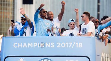 Kapten Manchester City, Vincent Kompany (tengah) bersama rekan setimnya melambaikan tangan dari atas bus beratap terbuka saat melakukan parade merayakan keberhasilan menjadi juara Liga Primer Inggris di Manchester, Senin (14/5). (Anthony Devlin/PA via AP)