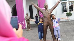 Dua anak berfoto dengan patung Presiden pertama RI Sukarno dipajang di depan Museum Fatahillah, kawasan Kota Tua, Jakarta, Rabu (15/11). Patung karya seniman Dolorosa Sinaga itu dibuat dengan bahan Resin. (Liputan6.com/Immanuel Antonius)