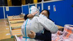Pasien virus corona atau COVID-19 Ying memeluk petugas medis Cao Jinglei di sebuah rumah sakit sementara di Wuhan, China, Senin (9/3/2020). China menutup semua rumah sakit sementara yang dibuat untuk menangani virus corona di Kota Wuhan.  (Xinhua/Shen Bohan)