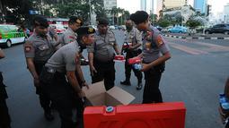 Aparat kepolisian yang melakukan penjagaan mendapatkan makanan berbuka puasa dari relawan TKN Jokowi-Ma'ruf Amin di kawasan Bundaran HI, Jakarta, Jumat (24/5/2019). Kegiatan ini sebagai bentuk kepedulian untuk aparat yang telah menjaga keamanan di Jakarta. (Liputan6.com/Angga Yuniar)