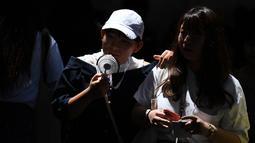 Seorang wanita memegang kipas portabel selama gelombang panas saat melintas di distrik Shibuya Tokyo pada Minggu (4/8/2019). Setelah menyerang beberapa wilayah di Eropa, suhu tinggi juga terjadi di Jepang. (Charly TRIBALLEAU / AFP)