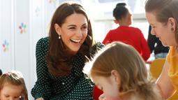 Kate Middleton tertawa saat bermain dengan pasien anak di Rumah Sakit Anak Evelina di London, Inggris (11/12).Kate dan suaminya pangeran William mengajak para pasien anak untuk merayakan Natal. (Chris Jackson/Pool via AP)