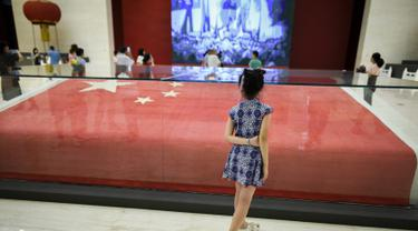 Seorang gadis melihat bendera nasional Tiongkok yang dikibarkan pada 1 Oktober 1949 di Lapangan Tiananmen di Museum Nasional China di Beijing (22/8/2019). Negara itu akan merayakan peringatan ke-70 berdirinya Pendirian Republik RakyatTiongkok pada tanggal 1 Oktober 2019. (AFP Photo/Wang Zhao)