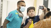 Pemain bintang sekaligus bek veteran Brasil, Dani Alves, melayani permintaan fans untuk foto bersama.  (Foto:AFP/Charly Triballeau)