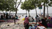 Sejumlah keluarga berkumpul menghabiskan waktu dikawasan pantai Ancol, Jakarta, Jumat (14/4). Warga Jakarta dan sekitarnya memanfaatkan liburan panjang untuk rekreasi bersama keluarga di Ancol. (Liputan6.com/Faizal Fanani)