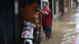 Warga beraktivitas saat banjir di Jalan Kebon Pala, Kampung Melayu, Jatinegara, Jakarta Timur, Rabu (7/2). Setelah sempat surut, banjir kembali merendam permukiman warga dengan ketinggian air mencapai sekitar 170 cm. (Liputan6.com/Arya Manggala)