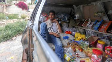 Majd al-Din al-Shamiri (16) menunggu pembeli di toko darurat di kawasan Jabal Sabr, Yaman pada 28 September 2019. Majd al-Din al-Shamiri mengubah mobil keluarganya yang rusak parah, akibat perang yang melanda, menjadi toko darurat untuk membantu keluarganya mencari nafkah. (Ahmad AL-BASHA/AFP)