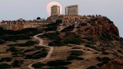 Pengunjung menyaksikan pemandangan bulan purnama hampir penuh yang menampakkan diri di langit Kuil Poseidon kuno di Cape Sounion, sekitar 70 kilometer sebelah tenggara Athena, Yunani (2/8/2020). (Xinhua/Marios Lolos)