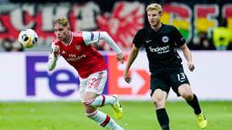Gelandang Arsenal, Emile Smith, berebut bola dengan bek Eintracht Frankfurt, Martin Hinteregger, pada laga Europa League di Frankfurt, Kamis (19/9). Frankfurt kalah 0-3 dari Arsenal. (AFP/Daniel Roland)