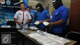 Dua orang tersangka penyelundupan narkotika asal Malaysia memperlihatkan barang bukti berupa sabu dan ekstasi, Jakarta, Rabu (17/6/2015). Tersangka yang merupakan ayah dan anak yaitu M (48), dan RMR (21) telah diamankan BNN. (Liputan6.com/Johan Tallo)