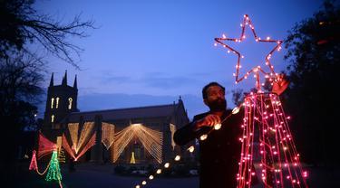 Seorang pria memasang dekorasi lampu di luar sebuah gereja di Peshawar, Pakistan barat laut (14/12/2020). Menyambut Natal, warga Pakistan mendekorasi rumah atau tempat ibadah agar lebih indah. (Xinhua/Umar Qayyum)