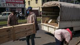 Tukang kayu memasukkan peti mati yang telah dipesan ke mobil di jalan raya umum, di Antananarivo, Madagaskar, Rabu (14/4/2021). Selama tiga minggu terakhir, Pak Jean dan timnya memproduksi antara 15 hingga 20 peti mati per hari, padahal sebelumnya hanya 3 atau 4 peti mati per hari. (RIJASOLO/AFP)