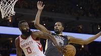 Aksi pemain Rockets, James Harden mengecoh pemain Warriors, Kevin Durant pada gim keempat final NBA basketball Wilayah Barat di Oracle Arena, Oakland (22/5/2018). Rockets menang 95-92. (AP/Marcio Jose Sanchez, Pool)