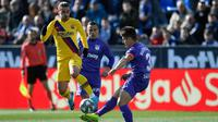 Striker Barcelona, Antoine Griezmann, berebut bola dengan bek Leganes, Unai Bustinza, pada laga La Liga Spanyol di Estadio Municipal Butarque, Leganes, Minggu (23/11). Leganes kalah 1-2 dari Barcelona. (AFP/Pierre-Philippe Marcou)