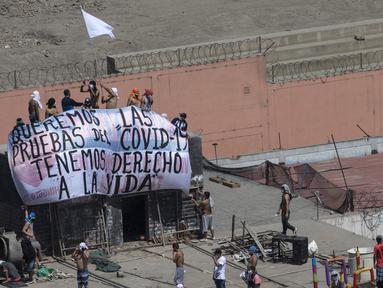 "Narapidana membentangkan spanduk bertulis ""Kami ingin tes COVID-19, kami memiliki hak untuk hidup"" saat protes di Penjara Lurigancho, Lima, Peru, Selasa (28/4/2020). Narapidana mengeluhkan pihak berwenang tidak berbuat cukup untuk mencegah penyebaran COVID-19 dalam penjara. (AP Photo/Rodrigo Abd)"
