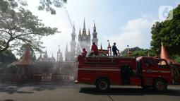 Petugas pemadam kebakaran melakukan penyemprotan cairan disinfektan tempat wisata di Taman Mini Indonesia Indah (TMII), Jakarta, Rabu (10/6/2020). Rencananya, TMII kembali dibuka untuk umum pada 20 Juni 2020 dengan menerapkan tatanan kenormalan baru. (merdeka.com/Imam Buhori)