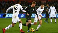 Bek Manchester City, Kevin De Bruyne menggiring bola dengan kawalan pemain Swansea City pada lanjutan Premier League di Liberty Stadium, Rabu (13/12). Man City mencatatkan rekor 15 kemenangan berturut-turut usai menang 4-0. (GEOFF CADDICK / AFP)