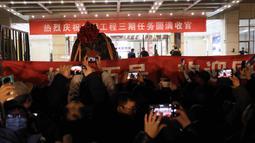 Orang-orang merayakan kedatangan kapsul pembawa pulang (return capsule) wahana antariksa China, Chang'e-5, di Akademi Teknologi Luar Angkasa China di Beijing, ibu kota China (17/12/2020). Sampel Bulan yang dibawanya akan dikirim ke tim peneliti untuk dianalisis serta dipelajari. (Xinhua/Jin Liwang)