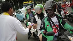 Relawan Millennial Jokowi-Amin membagikan coklat kepada pengendara roda dua dan empat di kawasan Patung Kuda, Jakarta, Kamis (18/4). Kegiatan tersebut sebagai bentuk terima kasih kepada seluruh anak bangsa yang telah ikut memberikan suaranya di TPS. (Liputan6.com/Faizal Fanani)