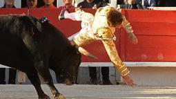 Seorang matador dari Prancis Andy Younes terpental saat ditanduk oleh banteng Spanyol Jandilla saat kompetis Feria du Riz di Arles, Prancis (4/1). Matador gagal menaklukan sang banteng. (AFP/Boris Horvat)