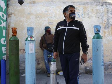 Jorge Perez antre mengisi tangki oksigen untuk anggota keluarga yang sakit COVID-19 di Mexico City pada 27 Desember 2020. Lonjakan pasien yang dirawat karena infeksi virus corona di Mexico City membuat toko pasokan medis kekurangan pasokan isi ulang tabung oksigen. (AP Photo/Ginnette Riquelme)