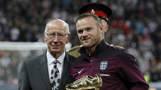 SEPATU EMAS - Wayne Rooney menerima penghargaan sepatu emas yang diserahkan langsung oleh Sir Bobby Charlton, Sabtu (10/10/2015) dini hari WIB. (AFP/IAN KINGTON).