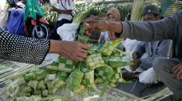 Pedagang kulit ketupat melayani pembeli di sekitar Pakualaman,Yogyakarta, menjelang Hari Raya Idul Fitri 1437 Hijriah, Senin (4/7). H-2 menjelang Lebaran, pedagang musiman yang menjual kulit ketupat mulai bermunculan. (Liputan6.com/Boy Harjanto)