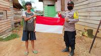 Suku Talang Mamak menerima bendera merah putih yang diberikan personel Polres Indragiri Hulu. (Liputan6.com/M Syukur)