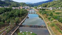 Foto dari udara menunjukkan tepian sungai yang telah direnovasi di Desa Zhikeng yang berada di Xiyang, Kota Meizhou, Provinsi Guangdong, China selatan (21/11/2020). Dalam beberapa tahun terakhir, Meizhou telah meningkatkan upaya untuk melestarikan lingkungan ekologis. (Xinhua/Li He)