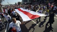 Pendukung oposisi Belarusia menggelar pawai bendera nasional saat berunjuk rasa di Minsk, Belarusia, Minggu (30/8/2020). Puluhan ribu demonstran berkumpul untuk menuntut agar Presiden Belarusia Alexander Lukashenko mengundurkan diri. (AP Photo)