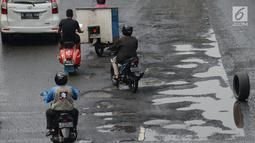 Sejumlah kendaraan melewati jalan berlubang yang masih tergenang air di ruas Jalan Lapangan Ros, Tebet, Jakarta, Sabtu (11/5/2019). Jalan-jalan berlubang yang terisi air tersebut dapat mengakibatkan kecelakaan bagi pengendara kendaraan bermotor. (merdeka.com/Imam Buhori)